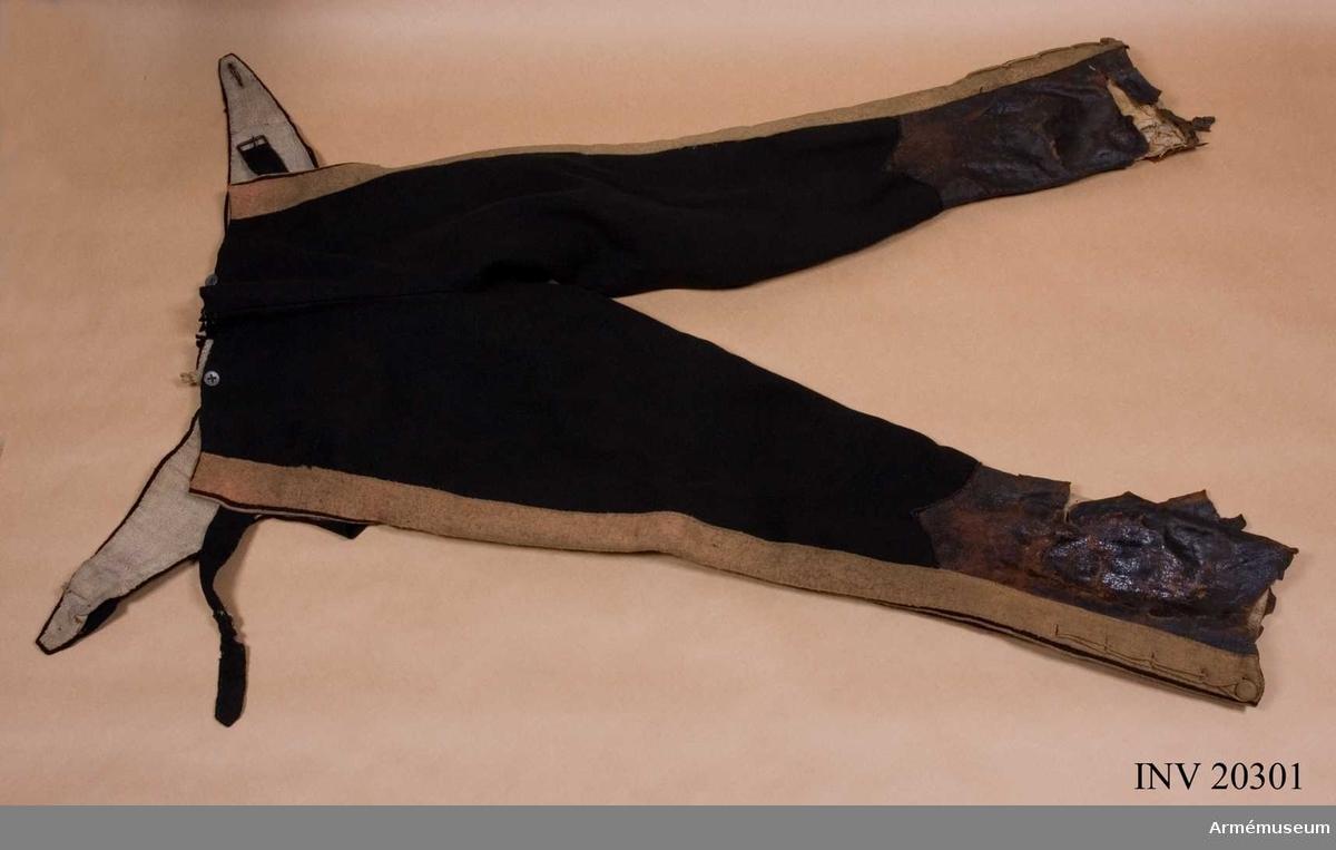 """Grupp C I. Ur uniform m/1817 för menig vid något av Gardets  infanterireg. Av svart kläde med dubbla gula klädeslister med mellanliggande gul passpoal på sidorna, s.k. lampasse. På byxbenens nedre delar finns skoning av läder med sprund och 5 snören. Foder av linnelärft. LITT  Armée Russe, Pajol, 1854. F von Stein, Geschichte des russischen Heeres, Hannover, 1885, sida 336: År 1817 fick dragonreg:t istället för mörkgröna byxor med knappar  byxor av samma kläde med """"lampasse"""" i kragens färg."""