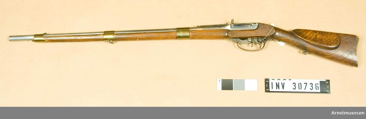 """Samhörande nr är 30736-8. gevär, bajonett, handtag.Studsare, kammarladdnings, Svea artillerireg. Grupp E II.  Antal räfflor är tolv. Räffelstigningen är 3/4 varv på piplängden. Rundkulans vikt: 30,6 gr, d:17,5 mm. Loppets rel. l: 49 kal.  Pipan har 12 cm långt, åttkantigt, framtill 16-kantigt, kammarstycke, men det långa fältet är runt. Ett silverkorn sitter fastlött 12,5 cm bakom mynningen. På undersidan finns en bajonettklack 7,3 cm och en stötklack 9,5 cm bakom pipmynningen. Siktet är ett till 1300 fot graderat fjädersikte och sitter vid bakre pipänden. Baktill är pipan inskruvad i framväggen på en uppåt öppen låda av järn.  På bakplanet har lådan en hake, som skall inhakas i hålet på svansjärnet. I lådan är kammarstycket anbringat. Kammarstycket är gråhärdat och 82 mm långt, 31 mm brett och 30 mm högt. Kammarstyckets utborrning har en diameter av 17,8 mm och mynnar ut i ett på kammarstyckets framplan placerat, 4 mm långt koniskt munstycke. En skena, vars ytterkanter går ut över lådans övre kanter, är fastnitad på kammarstyckets översida samt hindrar att det kommer för långt ned i lådan. I bägge pipväggarna 25 mm från lådans bakre kant och 6 mm från den övre lådan en 15 mm lång, oval urtagning. I var och en av dessa urtagningar går en i kammarstycket insatt skruv. Längs lådans vänstra sida ligger en lång fjäder, som framtill med en skruv är fäst vid lådan. Fjäderns bakre ände ligger över den ovan omtalade ovala urtagningen i vänstra väggen. En bit från bakänden har fjädern en kraftig tapp, som går in genom ett hål i lådväggen ett par millimeter framför den omtalade ovala urtagningen. Denna tapp går i ett på kammarstyckets vänstra sida befintligt spår, som först går rakt framåt, sedan i båge nedåt. På översidan en bit från framkanten har kammarstycket ett par i bredd sittande, utåtböjda handtagsknappar. På kammarstyckets undersida en bit från bakänden är knallhattstappen inskruvad. Framför lådans bakre vägg är en 11 mm tjock """"stötskiva"""" anbringad. Upptill till hög"""
