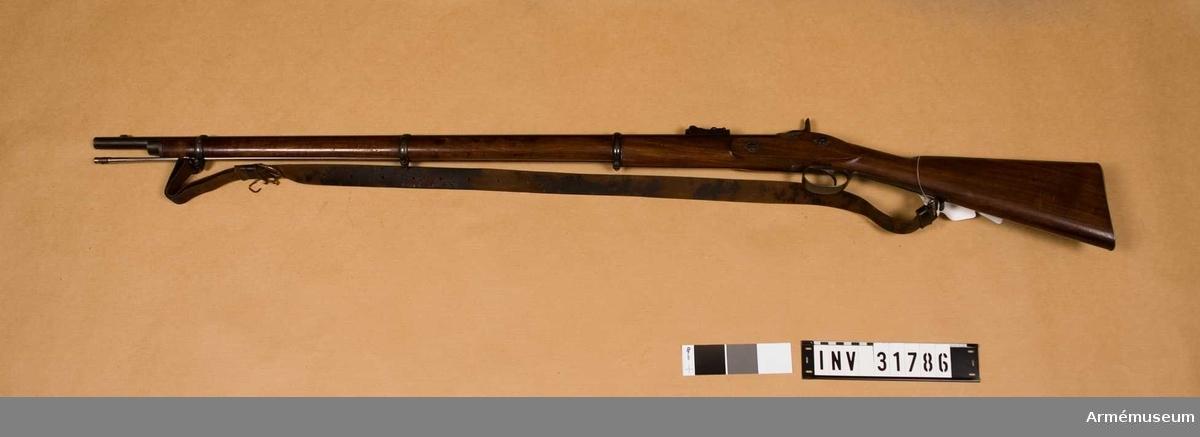 Grupp E II.   Räfflat med slaglås för bajonett. Relativ längd är 81,4 kaliber. Patentsvansskruv och kedjelås.  Samhörande nr är AM.031786-AM.031787, gevär, rem.