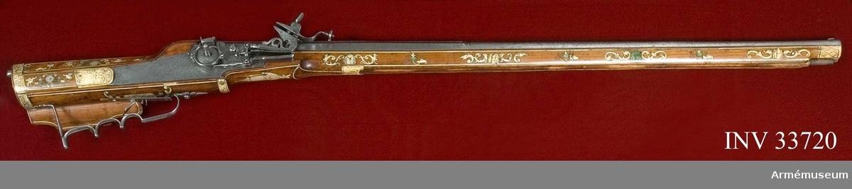 Grupp E II. Hjullåsstudare, tillverkad i 1600-talets början, Tyskland.  Antal räfflor 8 st. Pipan är åttkantig med något trumpetformad mynning. Den har ett klaftsikte och kon av järn.   Låset är helt av järn och låsblecket är dekorerat med djurmotiv. Hjulet är monterat på insidan av låsblecket.   Stocken är av polerad valnöt, rikt dekorerad med inläggningar av graverat hjorthorn och pärlemor. Beslagen är av järn.
