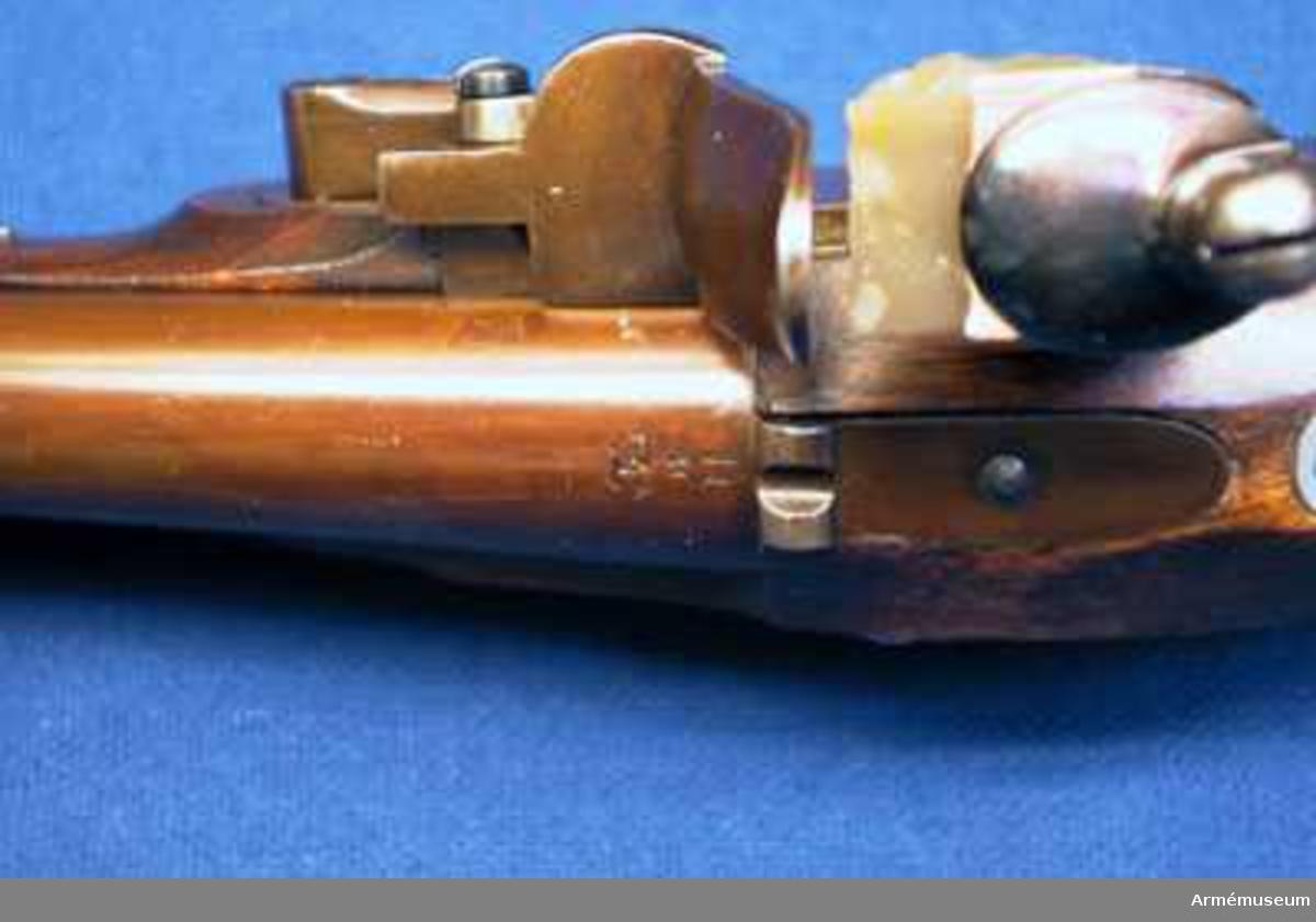 """Grupp E III c.  Med undantag av att pipan är slätborrad samt i fråga om siktet överenstämmer vapnet helt med den fullt beskrivna AM 34966. Loppets rel. l:16 kaliber. Den brungjorda pipan med korn och häfte liknar fullkomligt den på AM 34966, men stånd siktet har bred siktskåra. Baktill på pipans översida är inslaget H, M och dubbelt C och på undersidan står P,2 och kronstämpel. På pipans bakplan och på svansskruvsstjärten finnes en stämpel med POQ.Låset liknar fullkomligt motsvarande del på motsvarande del på AM 34966.  På bleckets insida finnes en stämpel med bokstäverna IBL och en otydlig kronstämpel. Stocken är av brunbetsad björk och överenstämmer med den på AM 34966. På undersidan till höger om varbygeln finnes inslaget  POQ och på vänstra sidan bakom sidblecket finnes några otydliga bokstäver och numret 967. Alla beslag likna motsvarande på AM 34966 På insidan av varbygelns främre arm sitter en stämpel med IV och på insidan av kappan, sidblecket och näs- bandet en stämpel med bokstaven E.  Pistoler m/1820 gå i par. Av varje par är den ena pistolen en slätborrad flankörpistol, även kallad blänkarepistol, av ovan beskriven typ, men den andra är en refflad studsarepistol (se AM 34966). Till varje par pistoler hörde en lös laddstock och en löskolv, vilka båda beskrivas under AM 34966.Till 1820 års flankörpistoler kunde användas rundkulor av samma kaliber som de, vilka användes till studsarepistoler m/1820, men egentligen voro de förstnämda vapnen avsedda att skjuta grova hagel, """"rännkulor"""". Krutladdningen till pistoler var ½ lod=6,65 gr.(Enander. Anvisningen till skjutkonsten med handgevär,sid. 131). En rännkula uppgavs 1832 ha en diameter av  0,37 decimaltum = 11 mm. Och en vikt av 0,6154 lod = 8,18 gr. (Enander, samma arbete sid. 27). Om dylika rännkulor användes till 1820 års flankörpistoler, är osäkert. Sannolikt hade de för dessa pistoler avsedda rännkulorna mindre kaliber. En komplett, med rännkulor laddad pistolpatron uppgavs väga 2 7/8 - 3 lod = 37,375 - 3"""