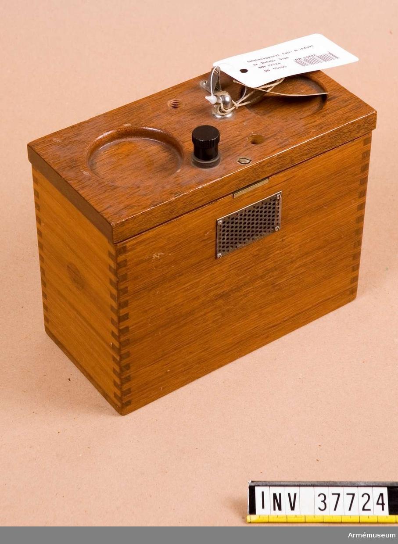 Grupp H I.   Av teak.Defekt. Bland annat så saknas handmikrotelefon, signalinduktor, en linjekontaktskruv och tangent på locket. Mått: 180x90x150 mm.
