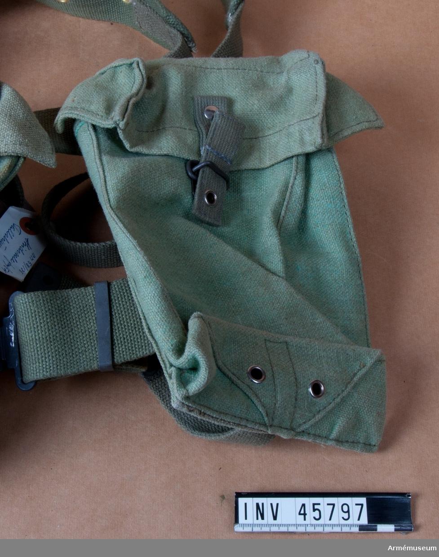 Grupp C I. Enhetsväska fm/1954. Typ I (stående) presenningsväv. Ur fallskärmsjägareuniform bestående av rock, stridsblus, byxor, sommarmössa, baskermössa, stålhjälm, skyddshjälm, marschskodon, två större ryggsäckar med mesar, stridssele, bälte, hängsle med sölja, två packfickor, mindre ryggsäck med två bärremmar, sidväska med bärrem, stridssele med två axelremmar, bärsölja, livrem, spänne, två enhetsväskor.