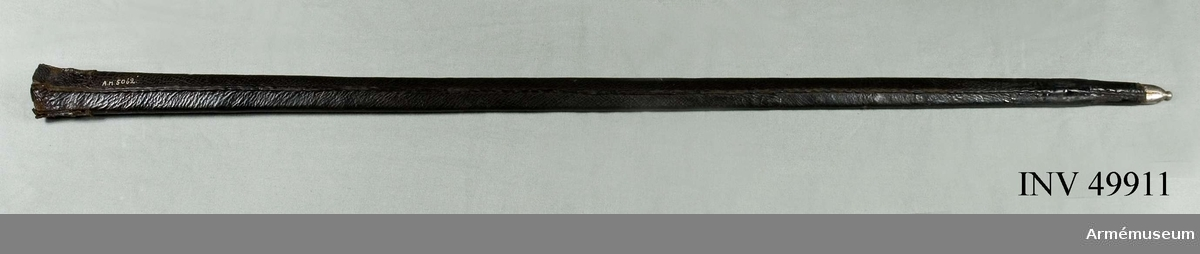 """Grupp D II.  Balja till karolinsk ryttarvärja av normaltyp. 1680-1740 ca. Baljan är klädd med svart läder samt har doppsko och koppelhake  av järn. Varbaljan är av svart skinn. På koppelhaken är siffran  3 inslagen. En fastklistrad lapp har påskriften: """"Under Officers  Värja med Järnfäste"""". Baljan har nedtill varit bräckt, men är nu  lagad.I 1879 års reversal kallas vapnet """"Värja, infanteri, svensk, 1690 års underofficers"""". Baljan kom från """"Baljor, sidogevärs, diverse sv läder"""". I 1813 års inventarium finns upptagna en """"Värja, Infanterie Under Officers 1690 års"""", en annan """"Värja, Under Officers 1690 års"""". I 1780 års inventarium finns upptaget en """"Underofficersvärja med stålfäste"""" och i 1759 års inventarium upptagas """"Ryttare wärjor med polerade Fästen, st. 3"""". (jfr AM 1932:7634).I Artillerimuseums inventarier betecknas vapnet 1879-1911 som """"Värja med balja m/1690 för underofficerare vid infanteriet"""". I 1912 års inventarium kallas värjan """"Värja med balja m/1685 med blankpolerat fäste, synes vara avsedd för officer eller under- officer"""". I 1914 års trycka katalog är beteckningen endast """"Värja med balja m/1685 med blankpolerat fäste"""", men på den vid värjan fästa kataloglappen, som var från samma tid, fanns tillägget """"för kavalleriet"""".Von Schreeb ansåg (ur Karolinska värjor, s 64), att detta vapen var en underofficersvärja. Samhörande nr är 49910-11, ryttarvärja, balja."""