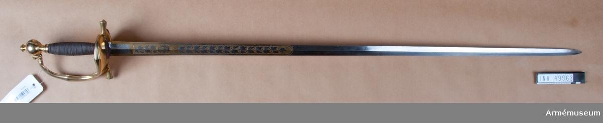 Grupp D II. Klingan är tveeggad med ryggar. På vardera sidan är den på en längd av omkring 32 cm prydd med blanka, etsade ornament på förgylld botten, däribland på yttersidan Karl XIV Johans namnchiffer och en ranka med lagerlöv, på insidan med tre kronor under kunglig krona samt en ranka med eklöv och ollon. Fästet är av förgylld mässing och av karolinsk kavallerityp. Knappen har formen av ett tillplattat klot samt har fram och bak en rygg markerad av en längs kanterna upphöjd rand. Nitknappen är rätt hög, svagt fasonerad och med ganska stor fot. Nedtill  fortsätts knappen av en på mitten instrypt hals. Runt halsens nedre del går en rand. Gränsen mellan hals och knapp samt mellan knapp och nitknapp är tydligt markerad. Kaveln omges upp- och nedtill av ett ringliknande, omkring 5 mm brett beslag av förgyllt mässingsbleck. Längs varje kant pryds dessa beslag av en ingraverad rand. I övrigt är kaveln lindad  med en tunn, av två parter hopsnodd försilvrad koppartråd. Parerstången vidgas rätt kraftigt mot de i trepass avslutade ändarna samt har ovalt tvärsnitt. Längs dessa övre och undre, främre och bakre kanter går en upphöjd rand. Parerplåten är hjärtformig. Dess förhöjda kanter är på mitten vidgade och har på samma ställe en kantig utbuktning på den mot plåten motsatta sidan. Handbygeln vidgas rätt kraftigt på mitten och har ovalt tvärsnitt. Dess övre ände är medelst en skruv fäst vid knappen. Längs över- och undersidan på de förhöjda kanterna samt längs handbygelns främre och bakre kant löper en upphöjd, smal rand. På översidan av parerplåtens yttre hälft är de ciselerade bokstäverna F J O (Frans Josef Oskar) fastnitade och på samma sida av den inre hälften är en kronprinskrona i liknande arbete fäst. Värjan är sannolikt en gåva från dåvarande Kronprins Frans Josef  Oskar, senare konung Oskar I, eller också har den tillhört denne  person. Liknande värjor bars även till salongsuniform av kavalleri- och artillieriofficerare, se AM 49987.  Samhörande nr är 49963-4, vär