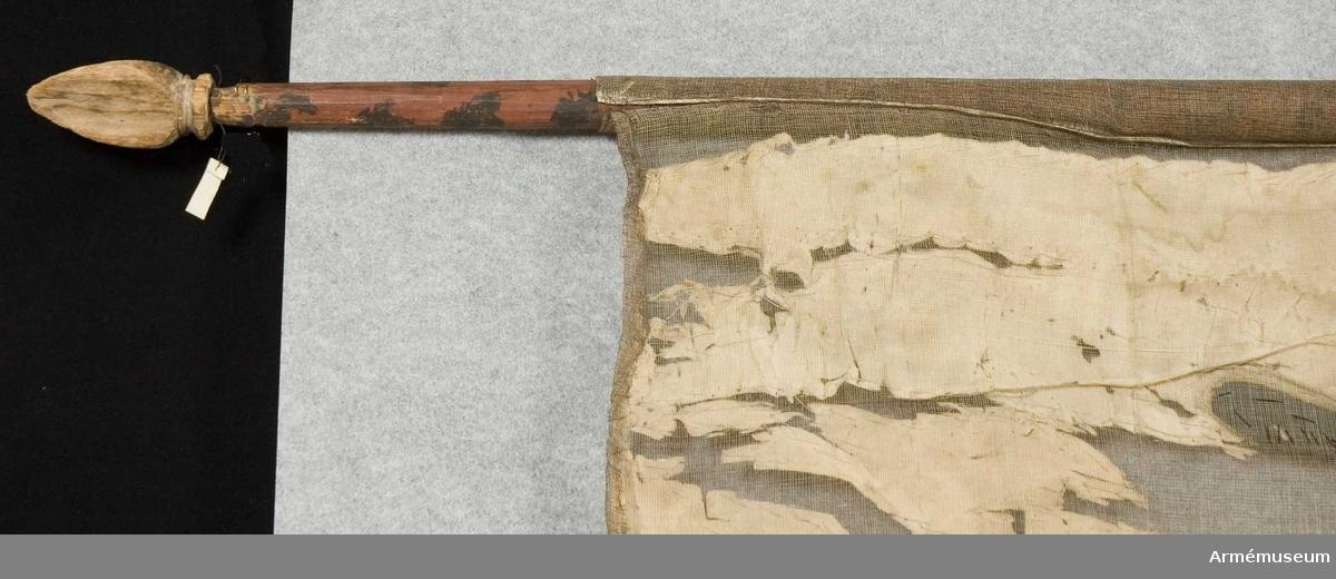Duk: Tillverkad av vit taft.   Dekor:  Ryska dubbelörnen.  Stång: Tillverkad av trä, brunmålad med svarta fläckar. Spets av trä, trekantig.