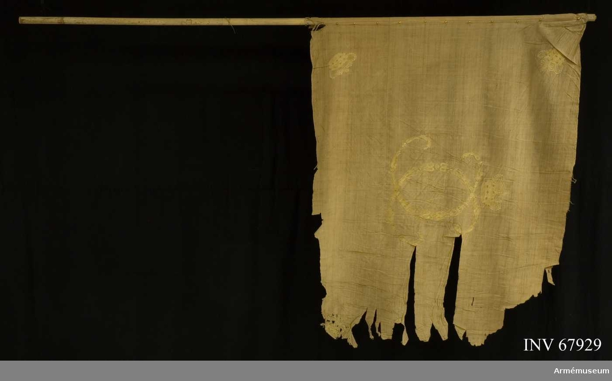 Duk: Enkel, tillverkad av vit linnelärft. Sydd av två horisontella våder.  Dekor:  Broderad med gult silke omvänt lika på båda sidor Karl XIV Johans namnchiffer, dubbelt C bildat av små ornament, omgivande XIV, under sluten krona med rött foder, i hörnen liknande kronor.  Kantad med vitt linneband. Fäst vid stången med glest satta tennlickor på ett kypertvävt linneband. Stång av vitmålad furu.