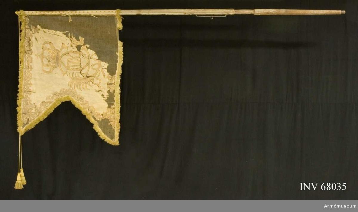 Duk: Enkel, tillverkad av vit sidendamast. Tvåtungad, sydd av två horisontella våder. Kantad med gul silkesfrans. Fäst vid stången med tre rader tennlickor på vita sidenband.  Dekor: Målat omvänt lika på båda sidor, Karl XII:s namnchiffer, dubbelt C under sluten rödfodrad krona, inneslutande XII. Däromkring två lyrformigt böjda palmkvistar, längs kanten en bård av palmkvistar och dubbla C liknande ornament, samt i hörnen små öppna kronor. Målat med konturer i rödbrunt.  Stång: Tillverkad av vitmålad furu. Kannelerad ovanför greppet.   Holk av förgylld mässing, fastsatt med tre spikar.  Banderoller: Tillverkad av gult silke, flätade med två tofsar som också är tillverkade av gult silke.