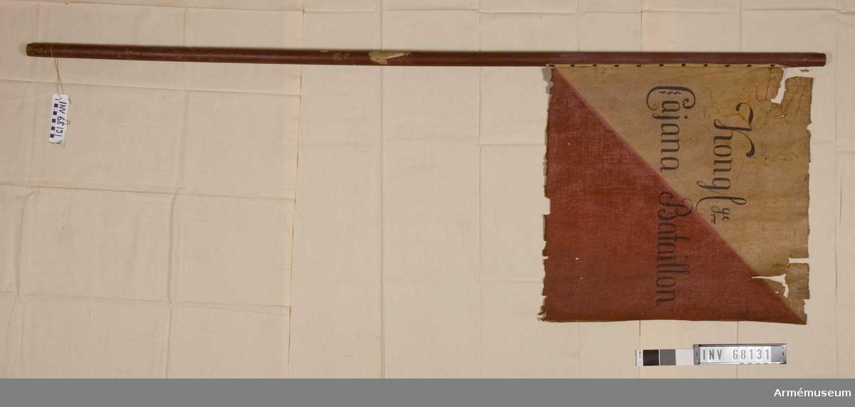 Duk: Tillverkad av enkel linnelärft. Målad, styckad i rött och gult nedre yttre delen röd, inre delen gul. Fäst vid stången med en rad tennlickor på en vit skinnremsa.  Dekor: Målad text i svart.  Stång: Tillverkad av rödmålad furu.