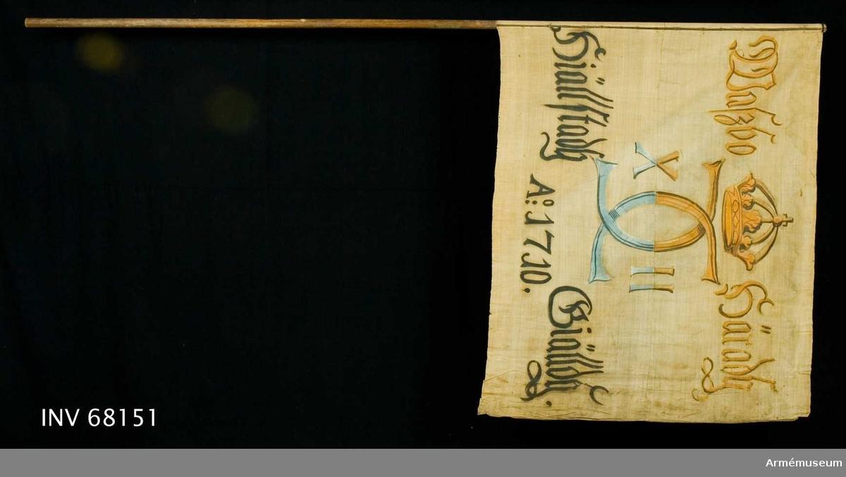 Duk: Tillverkad av enkel vit linnelärft, sydd av två horisontella våder. Fäst vid stången med en rad järnnagel på en liten brun läderremsa.  Dekor: Målad endast på dukens insida, Carl XII:s namnchiffer, dubbelt C med X-II på ömse sidor, krönt med sluten krona. I det övre fältet i gult och brunt, i det nedre fältet i svart och blått. Text på ömse sidor om chiffret, upptill i gult och brunt, nedtill i svart. Under chiffret text i svart.  Stång: Tillverkad av trä.