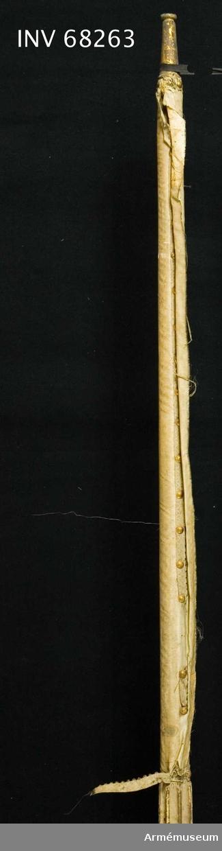 Fragment av vit sidenduk. Lindad runt stången, samt fäst med mönstervävt ca 15 mm brett band, under tennlikor av mässing. Rest av guldmålning finns, höjd: 950 mm. Nuvarande bredd: ca 20 mm.  Stång: Tillverkad av vitmålad furu, i lansform, kannelerad. Slätt handgrepp. Upptill holk av ursprungligt, förgyllt stål.
