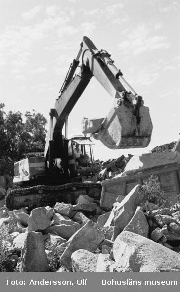"""Bohusläns samhälls- och näringsliv. 2. STENINDUSTRIN. Film: 47  Text som medföljde bilden: """"Skrotlastning med grävskopa. Truckarna för stenarna ner till Maersk Barge. Aug. 1977."""""""
