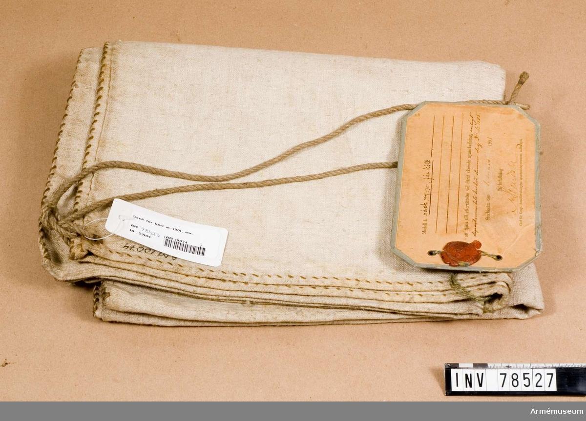 """Grupp I:III. Sidorna på säcken är sammanfogade med segelsöm. Vidhängande modellapp med text: """"Modell å säck m/01, för kött att tjäna till efterrättelse vid däraf skeende nyanskaffning enligt departementets beslut denna dag Dii Nr 1505. Stockholm den 1 mars 1901. På befallning:M Stendahl (?), Chef för Kongl. Arméförvaltningens intendentsdepartements militärbyrå"""""""