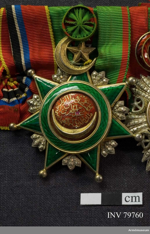 """Grupp M.  En sjuuddig, guldkantad, i ljusgrönt emaljerad stjärna med förgyllda kulor på spetsarne och hängande i en förgylld halvmåne med en femuddig stjärna. I vinklarna synas facetterade strålar av silver.  Åtsidan: Mittskölden består ytterst av en på båda sidor guldkantad ring av grön emalj; därinnanför synes på karmosinröd emaljbotten en förgylld halvmåne i hög relief och spetsarna sträckta uppåt, vidare, i inlagda guldtyper, sultanens namnchiffer samt ordensdevisen: """"Abdul Aziz Kahn, Turkiets härskare, som sätter sitt förtroende till Gud"""". Frånsidan: Mittskölden består av silver och innehåller överst en oval med i upphöjt arbete """"799 (arabiskt tecken)"""", nedanför två korslagda fanor och två trummor, ställda på kant.  Bandet: försett med kommendörsknapp, är bjärt grönt med två smala, karmosinröda kantränder.  Kompletterande beskrivnig Prn. Mått: Höjd, med halvmåne, 70 mm. Bredd 62 mm. Bandets bredd 36 mm."""