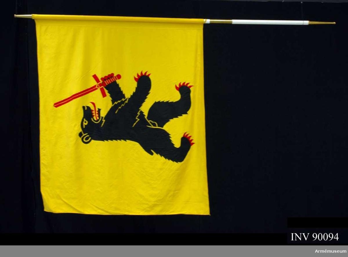 """På gul duk förbandets vapenbild: en upprest svart björn med röd beväring och med ett rött svärd i högra framramen.  Fanan är utförd i textil intarsia med maskinbroderade detaljer. Duken är av natursiden. Vitmålad, tvådelad stång med doppsko och holk av förgylld mässing.  På doppskon är ingraverat: """"Kalix försvarsområde Fo 67"""""""