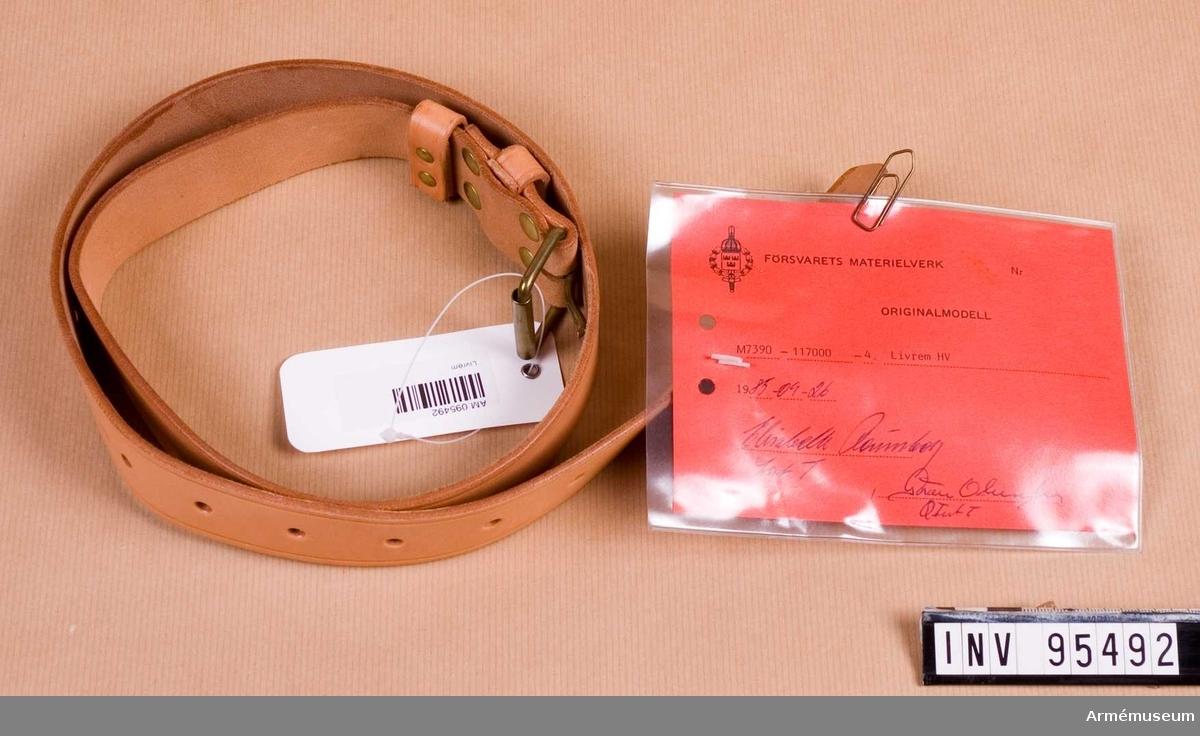 """Vidhängande etikett: """"Försvarets materielverk Originalmodell M 7390-117000-4, Livrem HV, 1985-09-26 (oläslig underskrift)""""."""