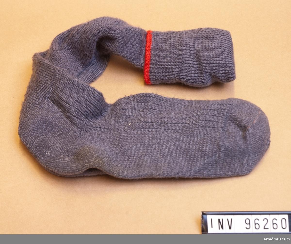 Ett par knäsockor i grå ull med röd kant.