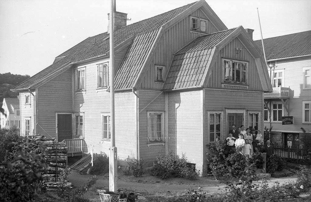 """Text till bilden: """"Hus med persongrupp, Karlsberg, Uddevalla. Den 23/7 1922""""."""