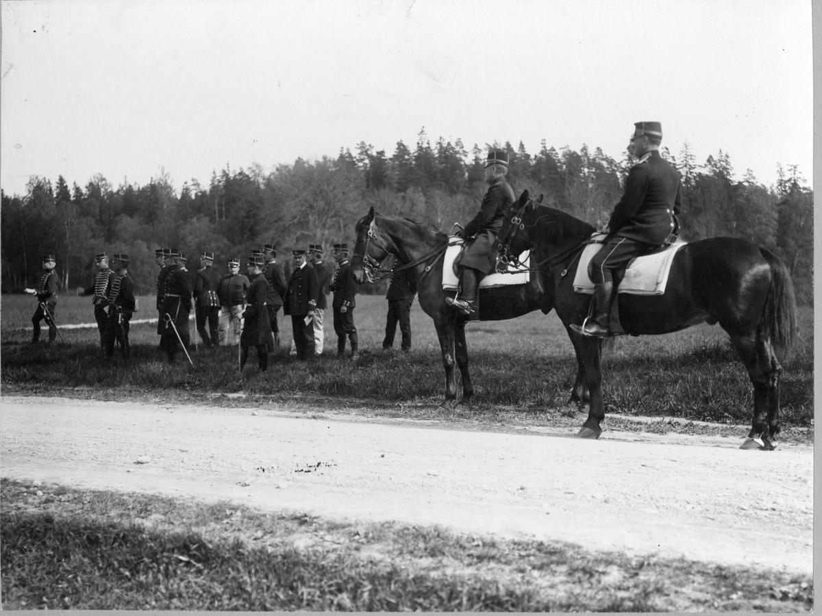 Två officerare till häst, tre husarer och ett antal officerare varav en sjöofficer står och väntar på något längs med landsväg.