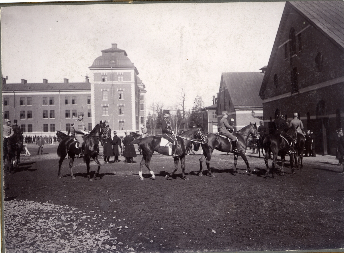 Trupp ur Livregementet till häst K 1, rider runt på kaserngården. Många åskådare ser på i bakgrunden.