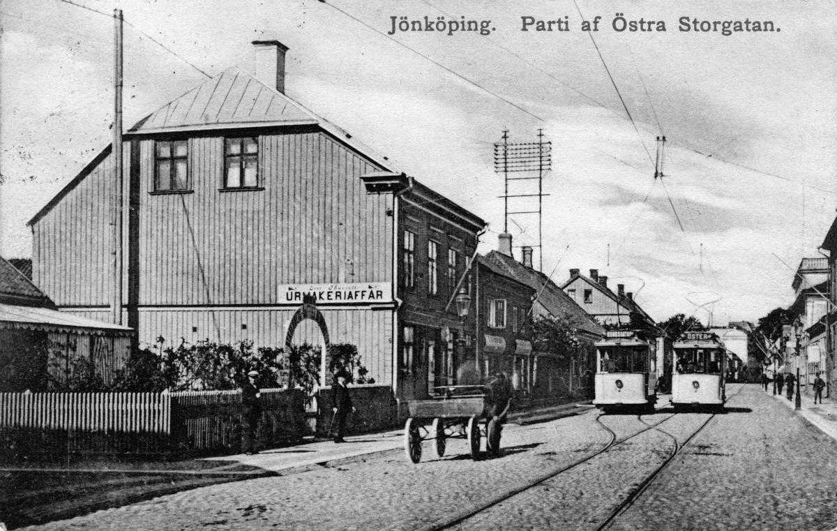 """Två spårvagnar och en hästkärra på Östra Storgatan i Jönköping. I huset till vänster finns en skylt med """"Urmakeriaffär"""". Vykort skickat 1910-02-27."""