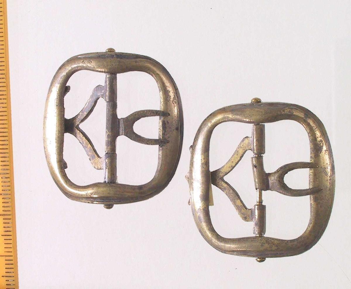 Knespenne,   Messing.  støpt.   Svakt buede,  bred ovale spenner,  glatte bortsett fra en  profillinje  langs kanten. Intakte hekter.    Lå i den ovale esken med signetene.
