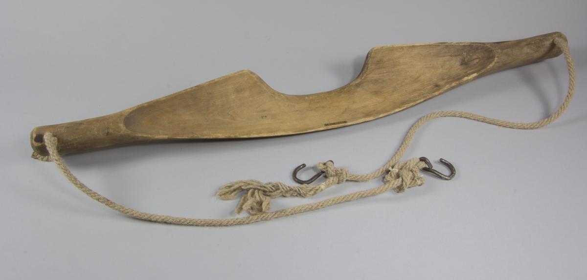 Ok, skuret av trä, furu eller gran. Hål i var ände, där rep med krokar sitter.