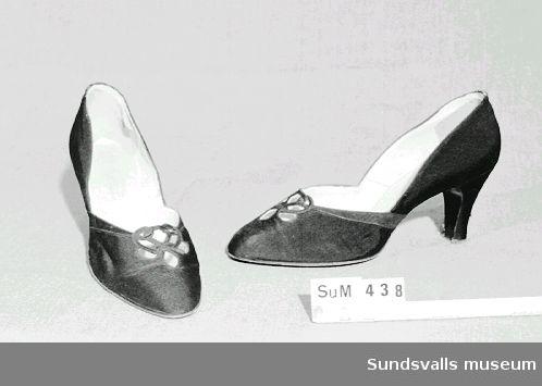 Ett par damskor i svart sidenrips. Märkning 'Bally Importe de Suisse' under skon och 'Chaussures de luxe Vente exclusive Bally pour la Suède AB Nordiska Kompaniet Stockholm' i skon.