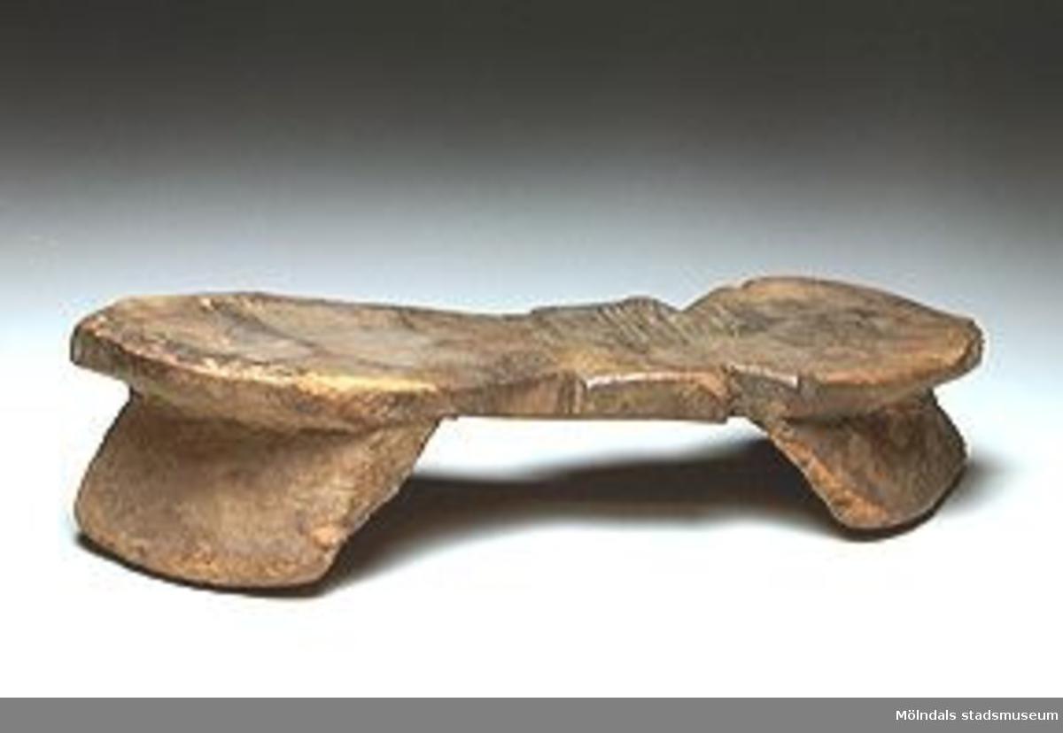 Mycket ålderdomlig hög träplatå som är fotformad, med ett hål för eventuell rem. Klövformad tå och  häl. Fördjupningar i träet av tårna. Funnen vid Isaks mosse i Lindome där man förr tog torv.