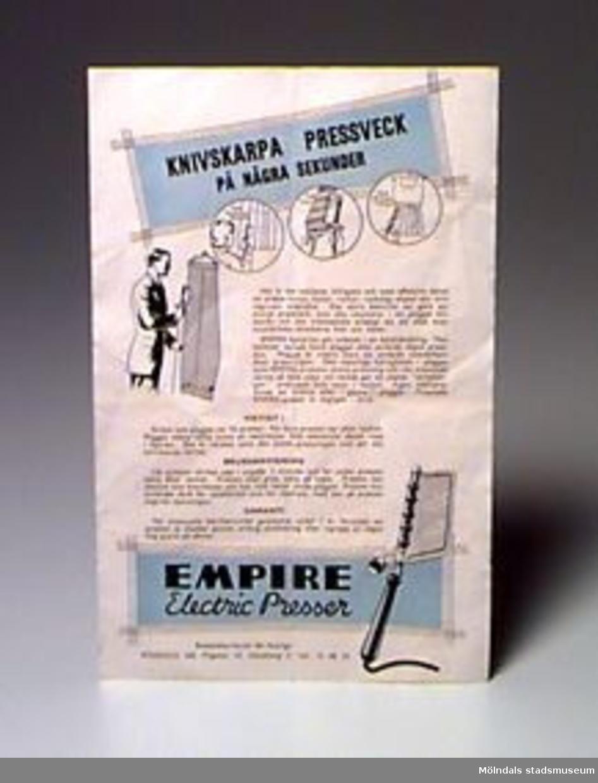 """Elektrisk byxpressare. Två plåtar sitter på en stång och bildar en klämma. Stången sitter fast i ett trähandtag med elektrisk sladd. Tillhörande bruksanvisning. Märkt: Empire Electric trouser presser British made 120 -130 volts. AC/DC.Ägaren/givaren inköpte apparaten i """"Lopplådan"""" i Krokslätt 1987."""