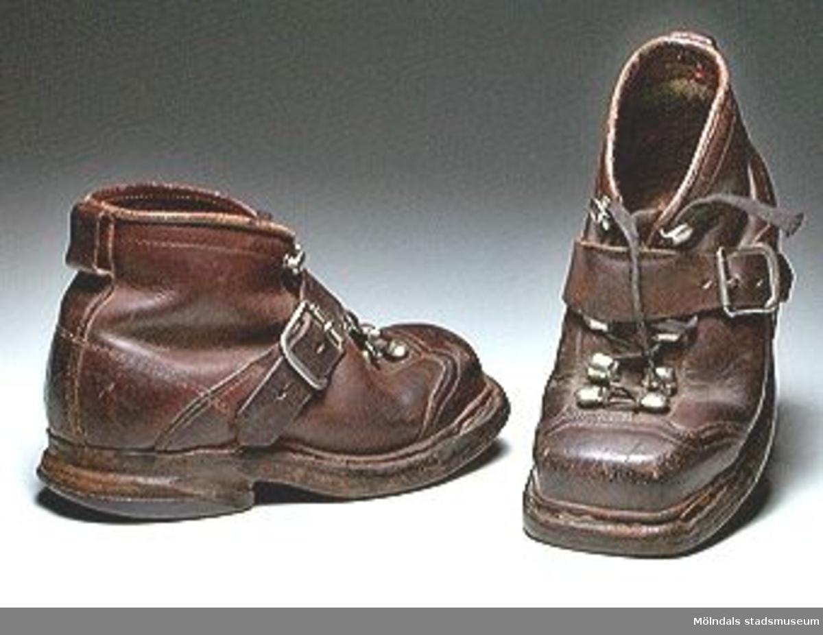 Ett par barnpjäxor i läder med gummiklack. Maskinsydda. Snörning. Rem. Storlek 29.Pjäxorna inköptes 1976 i en bytesaffär i Göteborg. Givarens två äldsta döttrar har därefter haft dem.