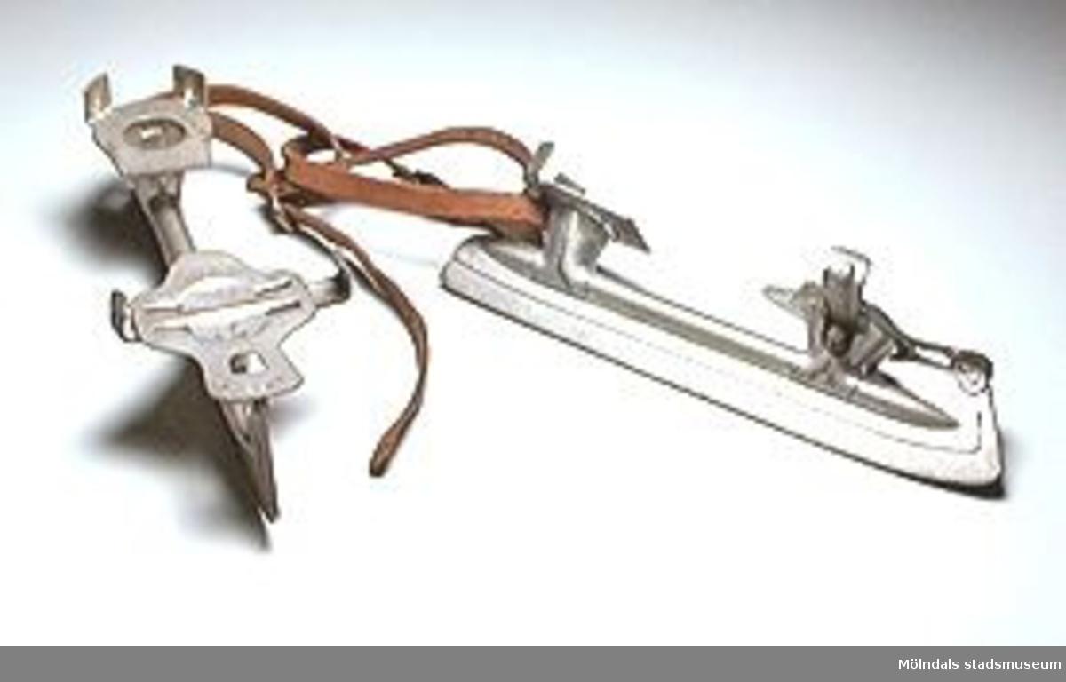 Ett par stålskridskor utan känga men med remmar. Med hjälp av en skruv kan sidokramporna ställas in till önskad bredd.Brukare/ägare är givarens morbror.