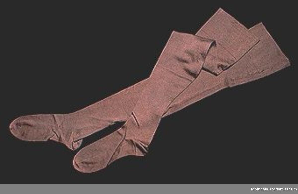 Gråbruna, lårhöga damstrumpor, att hållas uppe med strumpeband. Storlek ca 38-40 (gammal norm).