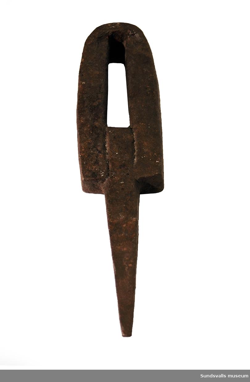 Järnkil med en spetsig del som sitter fast i en U-formad kropp. Tjocklek 4,3 cm. Redskapet användes av givarens far.