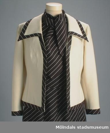 """Brun klänning med beige ränder. En matchande slips (fastsydd i klänningen) i samma tyg, en dräktjacka i beigt (fodret gulnat) tyg och ett skärp hör till. Det finns också tillhörande hatt, skor och tygkasse: invnr. MM03324, MM03325, MM03326.Givarens egna noteringar: """"Influenser från europeiska modehus flödade in i Sverige efter freden 1945. Modegalna unga damer släppte ner alla kjolfållar. """"New look"""" som tillät spetsunderklänningen att synas i ena kjolhörnet, bedårade mången ung herre. Min examensklänning - beige helplissé - lever endast kvar på examensfotot 1948. (Ner till anklarna.) Men under utbildningsåren 1946-1948 på Söteborgs Förskoleseminarium bar jag ofta vid föreläsningarna denna """"uniform"""". Kjol och jacka, alternativt klänning och jacka. Märke """"Radtke"""" (finskt). Lagom kjollängd till vardags. Ännu idag ej bevisat huruvida Radtke-märket eller seminarist Emilson (mitt flicknamn) drog till sig uppvaktande chalmerister i kö att köra pappas Packard. Plötsligt populär misstänkte jag då bilmärkets dragningskraft på körkortslösa pojkar - med mig vid ratten i glada 40-talets skolklädsel (""""uniformen"""").""""Måtten:Klänning MM03323:1: Längd 910 mm, bredd 440 mm (byst).Slips: Längd 450 mm, bredd 110 mm.Dräktjacka MM03323:2: Längd 525 mm, axelbredd 420 mm, armlängd 510 mmSkärp MM03323:3: Längd 855 mm, bredd 15 mm."""