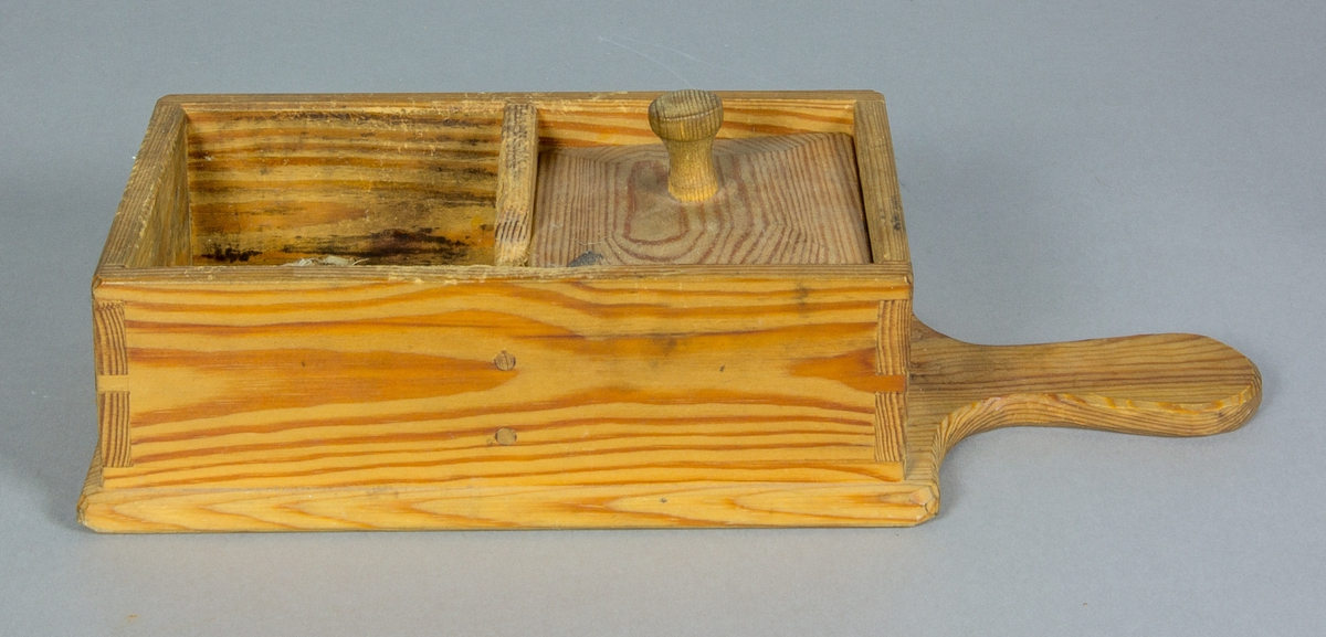 Skörask tillverkad av trä. Hopfogad med träplugg, laxade hörn. Asken har botten utdragen och formad till ett handtag. Den är inredd med två fack, varav det ena har ett lock med knopp. Mittväggen har en fördjupning mot ena kanten.