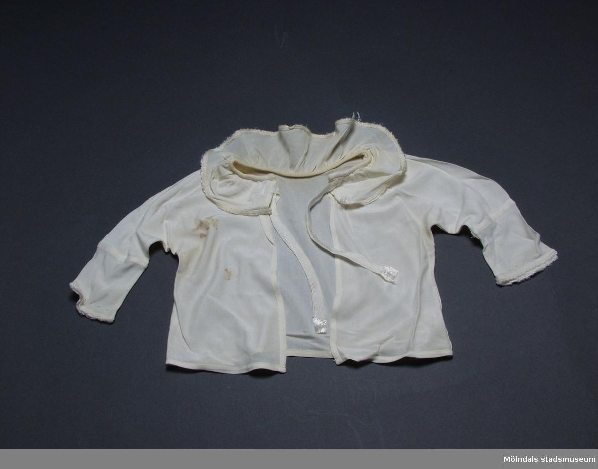 Spädbarnsskjorta i charmeuse, gulnad. Halsrysch och krage är kantade med en liten langett.