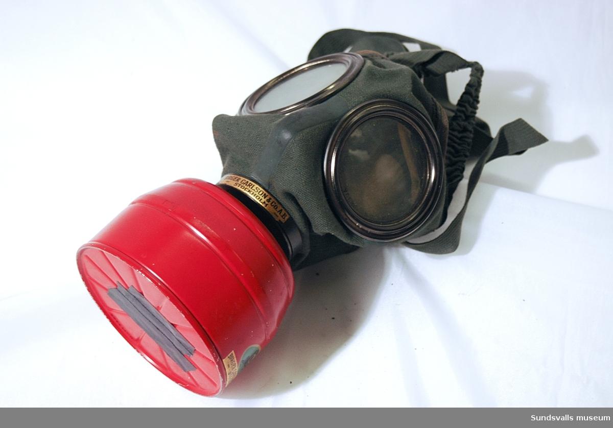 Gasmask/skyddsmask för ansiktet med filter mot föroreningar. Modellnamn 'Degea'. Förvaras i svart cylinderformad plåtbehållare med axelrem i brunt läder. I behållarens lock finns ett fack i vilket två sk. klarskivor förvaras i pappersomslag.  Masken är tillverkad av grönt bomullstyg i kraftig kvalitet, med runda metallinramade glas vid ögonen och en röd filterbehållare i metall. Invändigt är masken fodrad med sämskskinn. Masken spänns fast på huvudet med hjälp av resårband och reglerbara spännremmar.