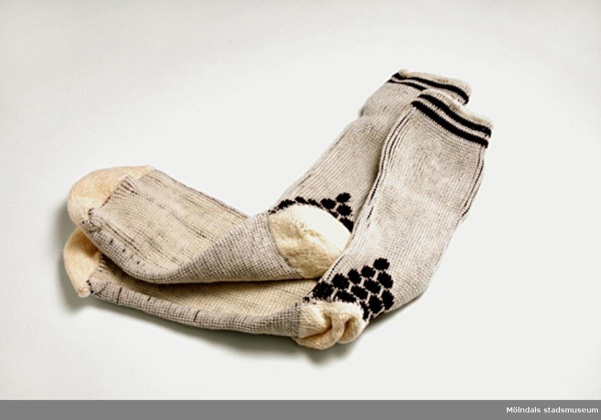 1 par ljusbeige bomullsstrumpor med två bruna ränder upptill på strumpan. Slätstickad i foten och resårstickad vid vristen. Mönster vid hälen.Storlek 37-40.