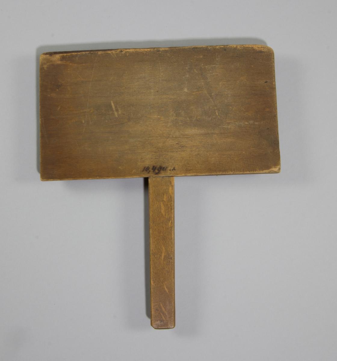 Karda i trä med piggar i metall. Rektangulär till formen med långt smalt handtag.