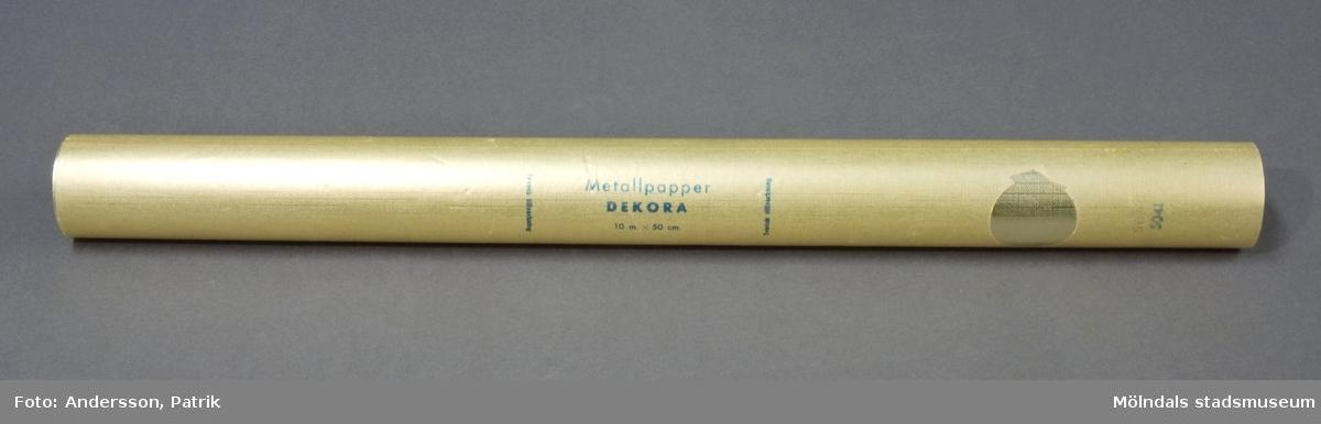 """Rulle, """"Metallpapper Dekora"""". Pappret är guldfärgat, ihoprullad i vaxpapper. Storlek: 10 m x 50 cm. Pappret är tillverkat på Papyrus i Mölndal.Litteratur: Papyrus 1895-1945, Minnesskrifter, Esseltes Göteborgsindustrier AB, Göteborg 1945."""
