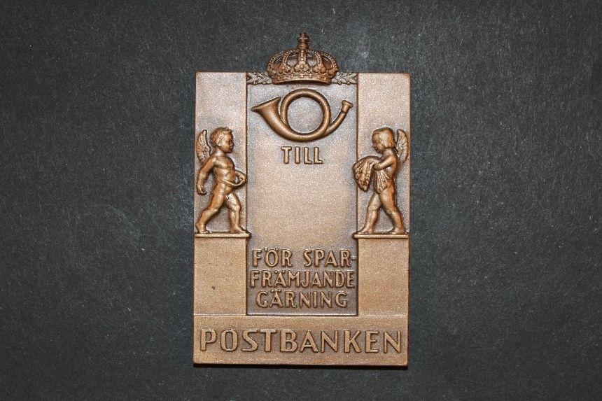 """Plakett, tillverkad i brons, utformad av konstnär KarlHultström. Rektangulär. Plaketten visar överst ett krönt postemblemav 1937 års modell. Under emblemet står text """"TILL .......FÖR SPARFRÄMJANDE GÄRNING"""". På bägge sidor om textfältet står två bevingade människor föreställande sådden och skörden. Underst stårtext """"SVERIGES POSTSPARBANK"""" flankerad av två uppsättningar avTre Kronor. Plaketten är märkt med tillverkarens namn (Sporrong)."""