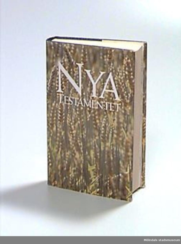 """Nya testamentet i Bibelkommissionens utgåva 1981. Blått konstläder med ett sädesax i guldtryck på pärmens framsida samt text i guld på ryggen. Skyddspapper med fotografi av sädesfält i närbild och text i vitt. På sidan tre en stämpel: """"Mölndals museum"""", samt skrivet med blyerts: """"C"""", ämneskod från museets bibliotek där boken tidigare var placerad."""