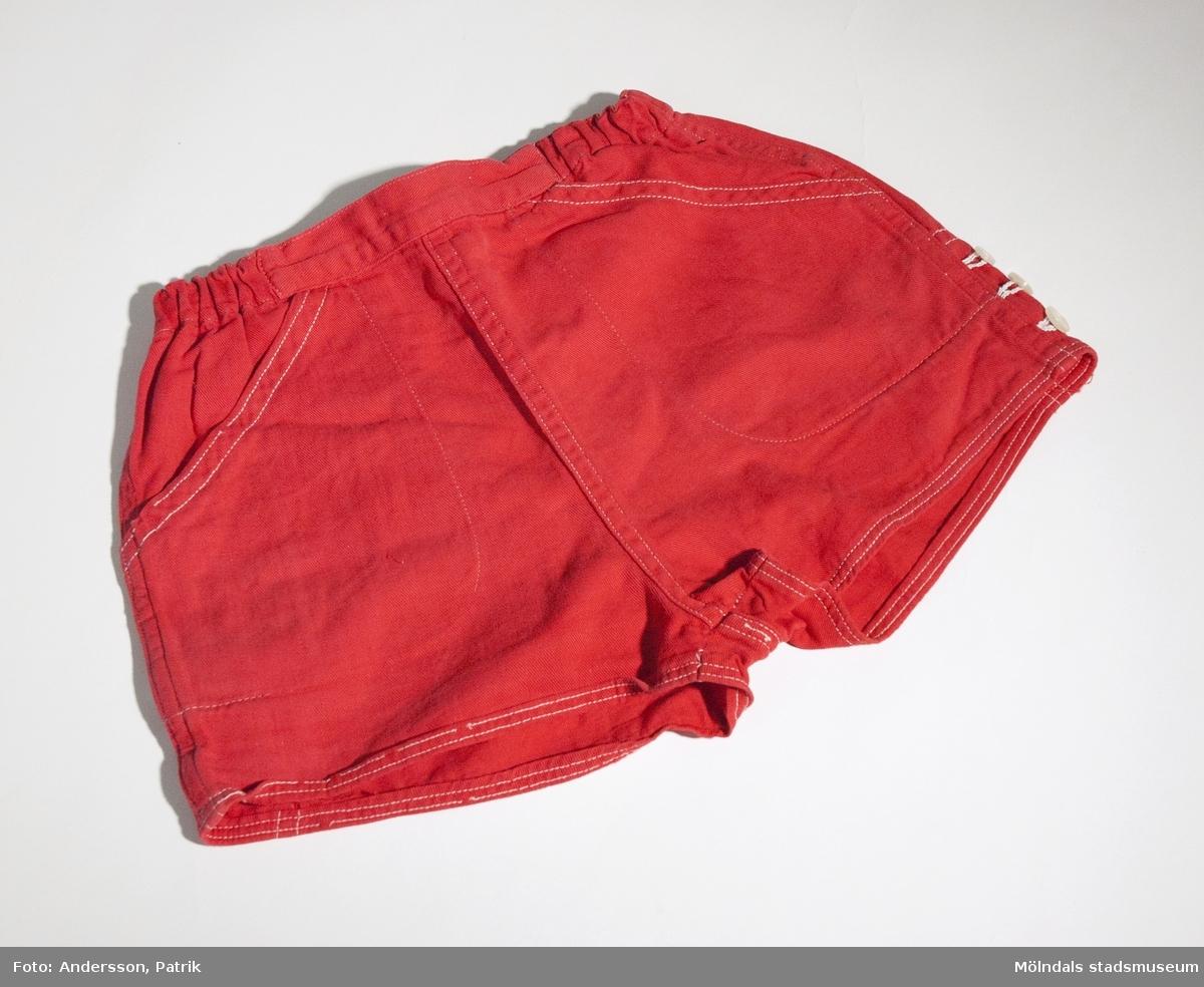 Röd bomullsbyxa för barn, kort sommarmodell. Sidofickor och dragsko i midjan.