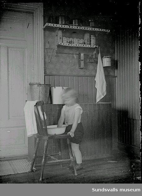 Pojke i köksmiljö, står vid en stol och  tvättar händerna i en balja.
