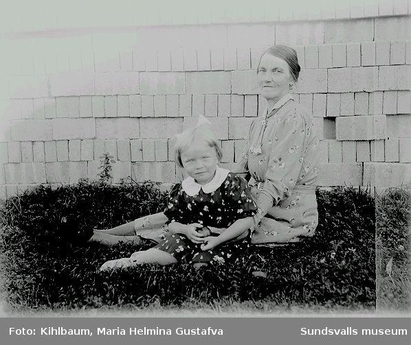 Porträtt av mor och dotter? som sitter i gräset.