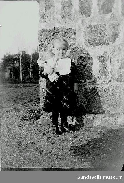 Porträtt. Liten flicka med docka i utemiljö.