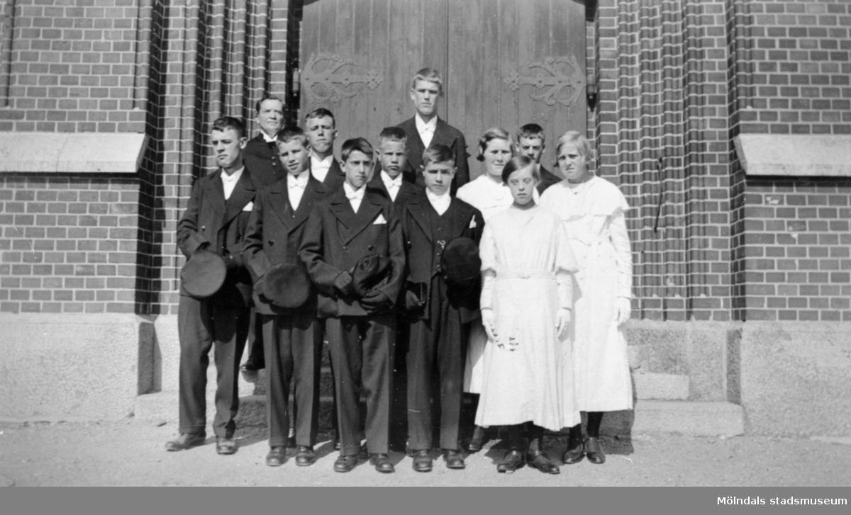 En konfirmandgrupp från Stretereds skolhem fotograferade framför porten till Fässbergs kyrka. Årtal okänt.
