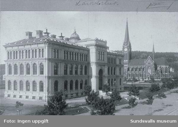 """Till vänster läroverket och till höger Skolhusallèn i bakgrunden Gustav Adolfskyrkan. Baksidan av fotot har bland annat texten """"J.Sunessons Bokhandel, Sundvall""""."""