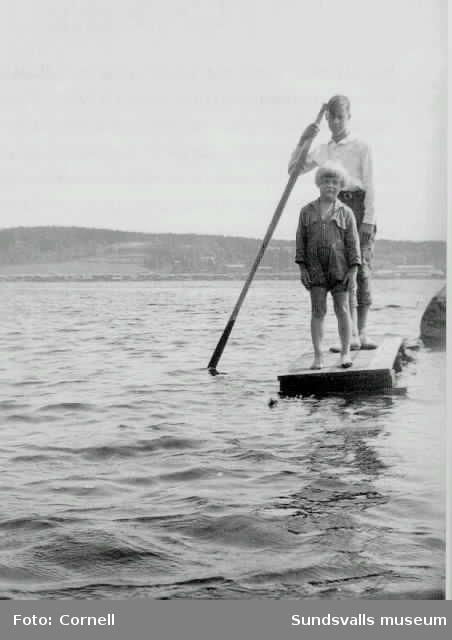 Jan och Guj på flotte. Karlsviks sågverk på Alnön med brädupplag i bakgrunden.